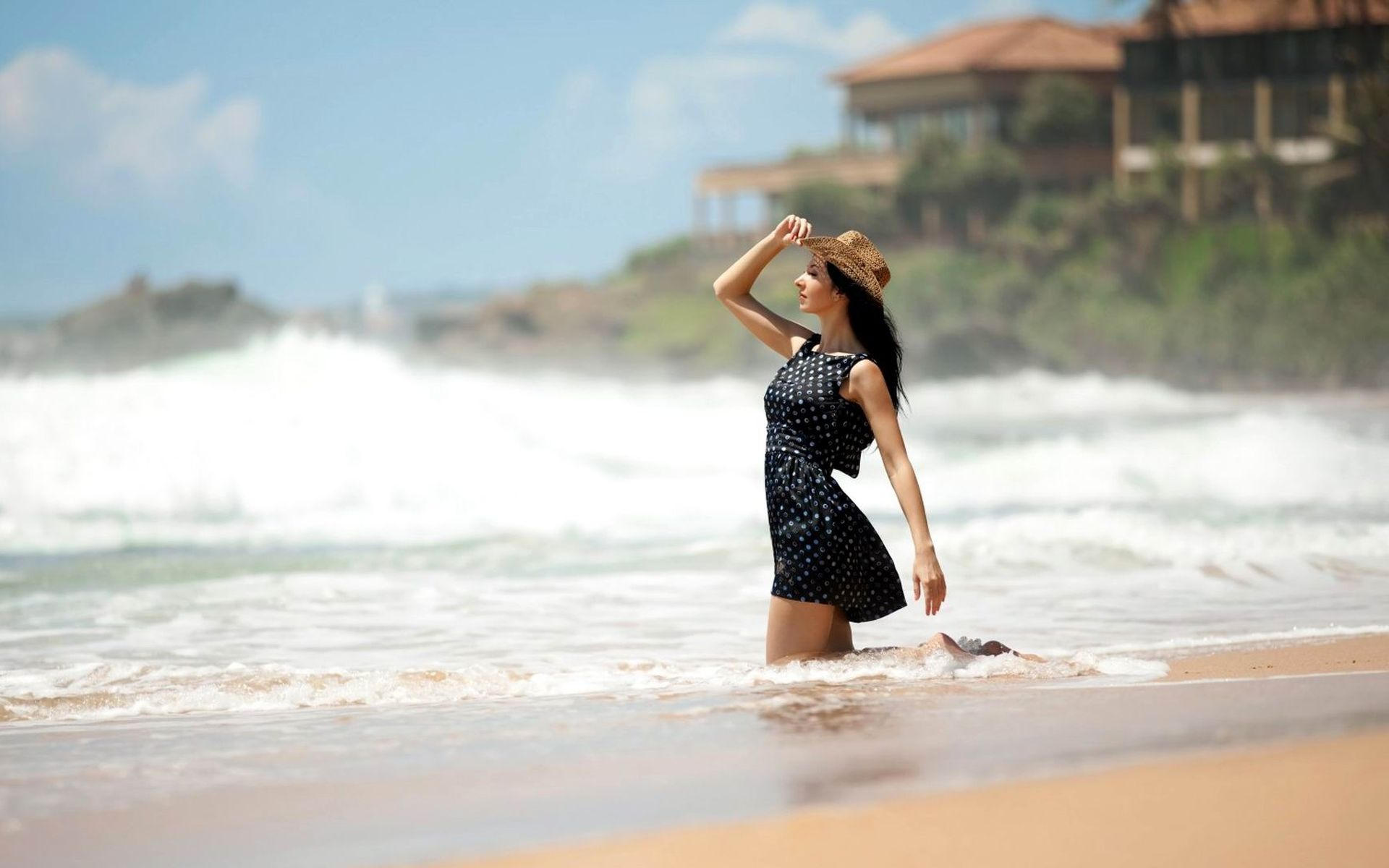 Женщина в шляпе и черном платье на берегу моря