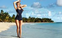 Женщина прогуливается по пляжу