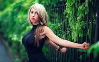 Блондинка схватилась руками за забор