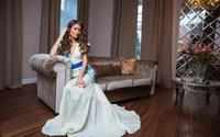 Девушка в белом платье мечтает на диване