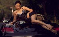 Изящная женщина на капоте дорогого авто