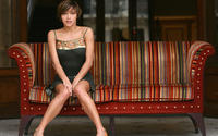 Брюнетка Эмма де Кон в платье на диване