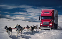 Упряжка собак тянет грузовик по снегу