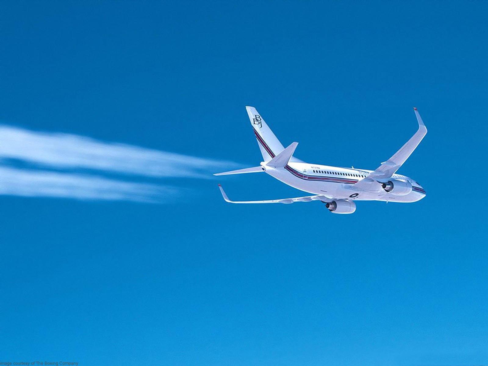 Самолёт летит на фоне синего неба оставляя след
