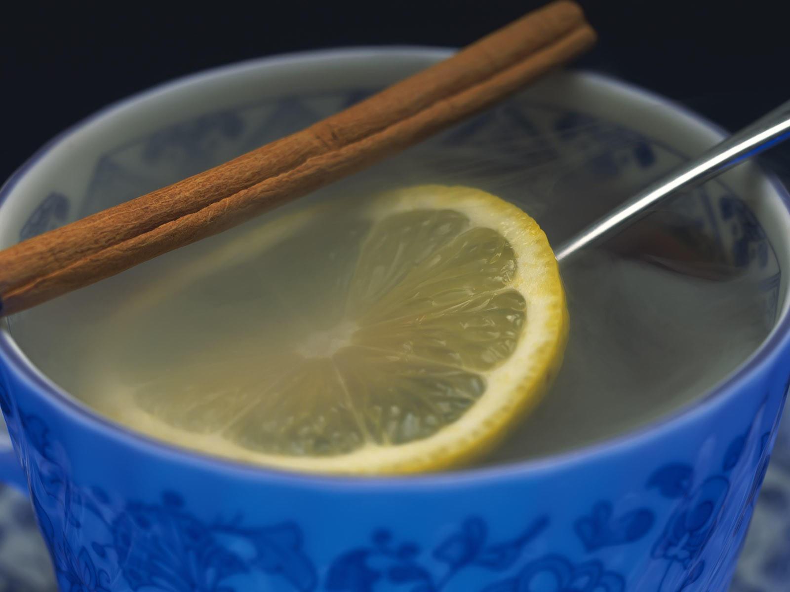 Чай в чашке с лимоном и корицей