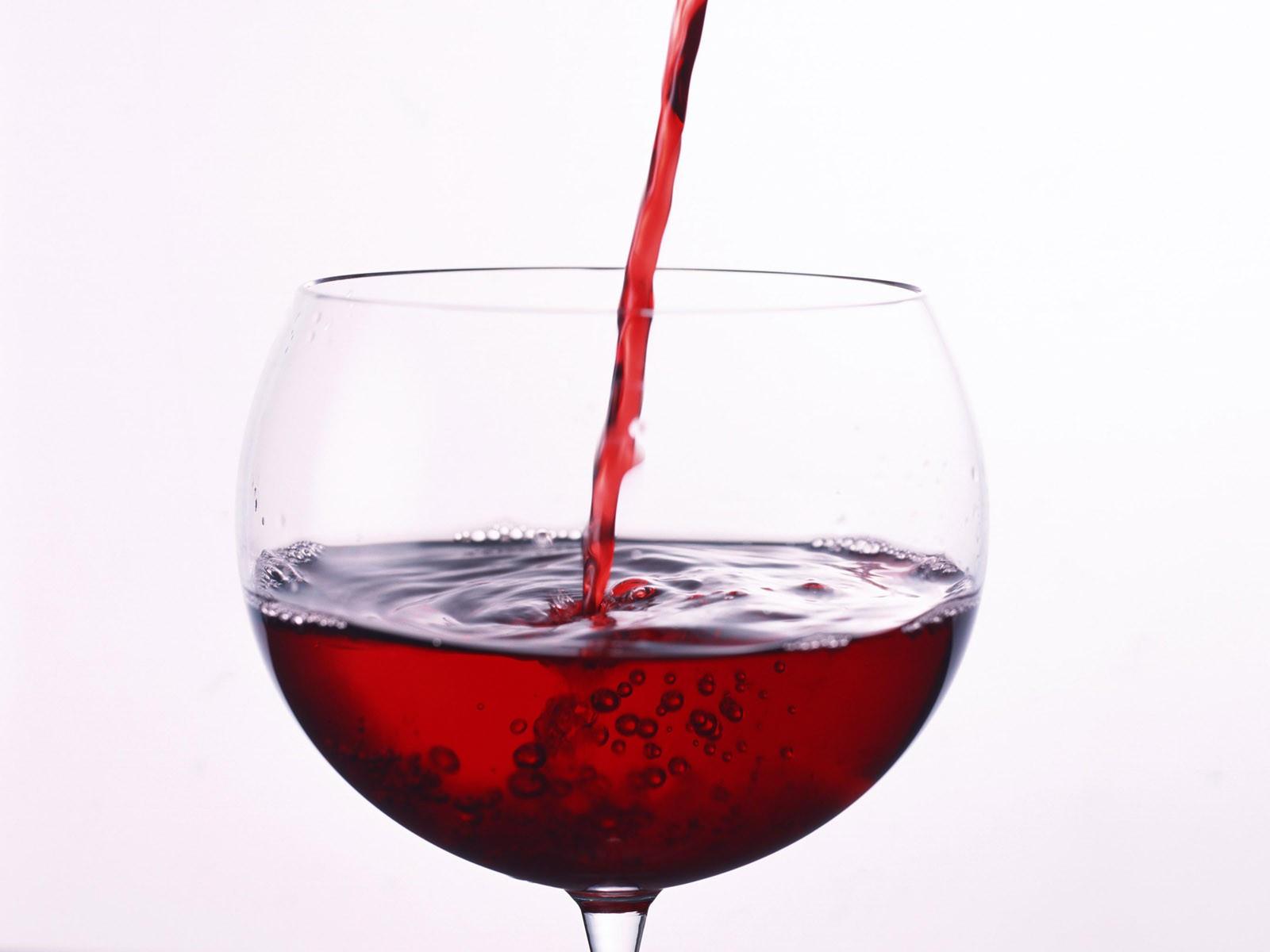 Бокал наполняют красным вином