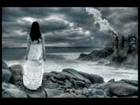 Девушка в белом на каменистом берегу