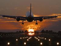 Авиалайнер стартует со взлетной полосы на закате