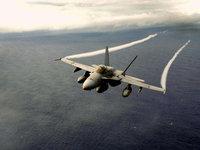 Военный истребитель оставляет белый след в небе