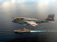 Гидросамолёт летит над авианосцем в море