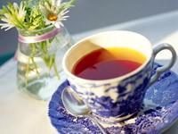 Чай в чашке и ваза с ромашками