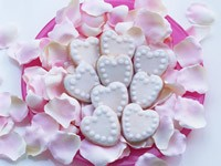 Печенье сердечки и лепестки роз на тарелке